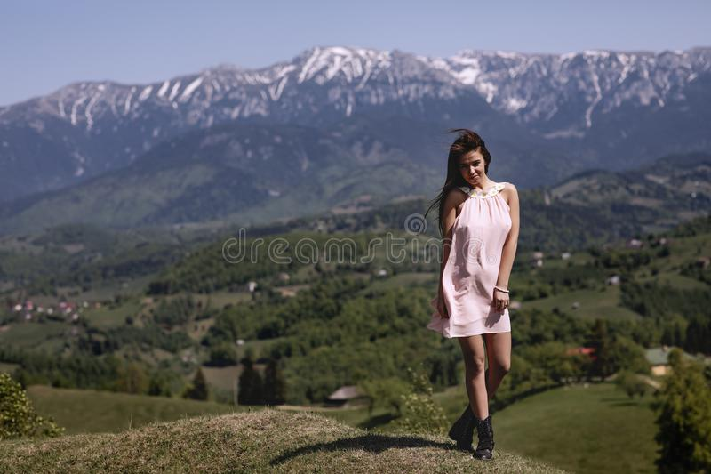 Una mujer hermosa en el vestido disfruta de la vista de un lan de la montaña fotografía de archivo