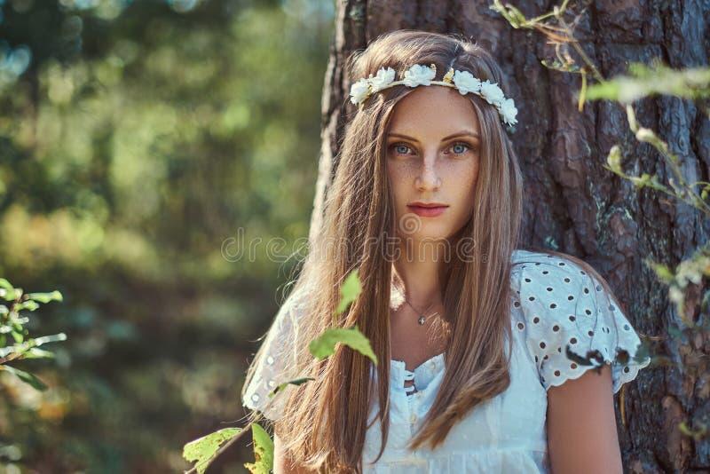 Una mujer hermosa en un vestido blanco y el blanco enrruellan en la cabeza que presenta en un bosque verde del otoño foto de archivo libre de regalías