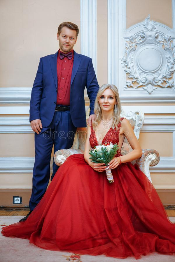 Una mujer hermosa en un vestido rojo con un hombre que se sienta en una silla, la novia y el novio, recienes casados felices foto de archivo libre de regalías