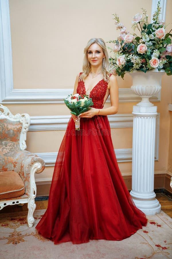Una mujer hermosa en un vestido rojo se coloca con un ramo de flores, la novia fotografía de archivo