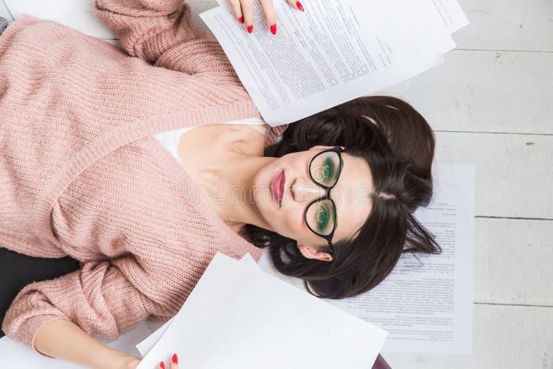 Una mujer hermosa en vidrios elegantes miente en el piso entre los papeles y los documentos, las sonrisas del freelancer de la mu imágenes de archivo libres de regalías