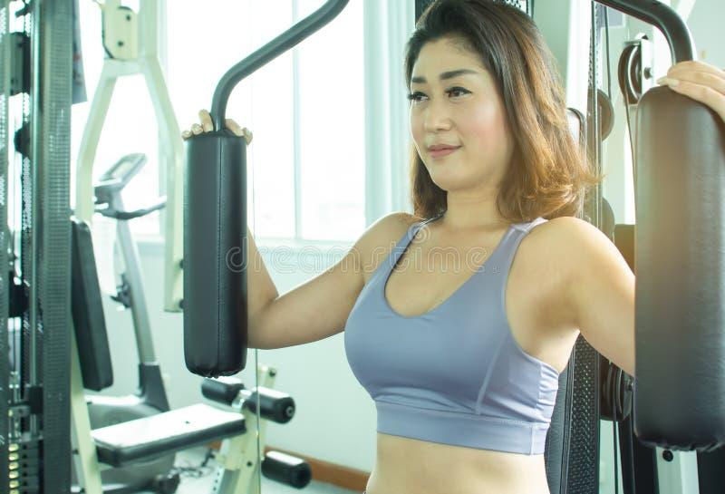 Una mujer hermosa está haciendo ejercicio en gimnasio imágenes de archivo libres de regalías