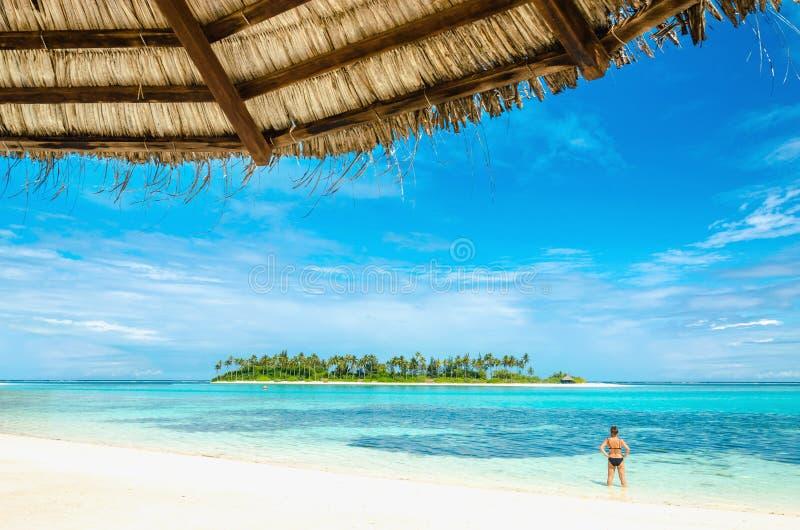 Una mujer hermosa está mirando una isla deshabitada exótica con una playa arenosa y palmeras altas con una palmera foto de archivo
