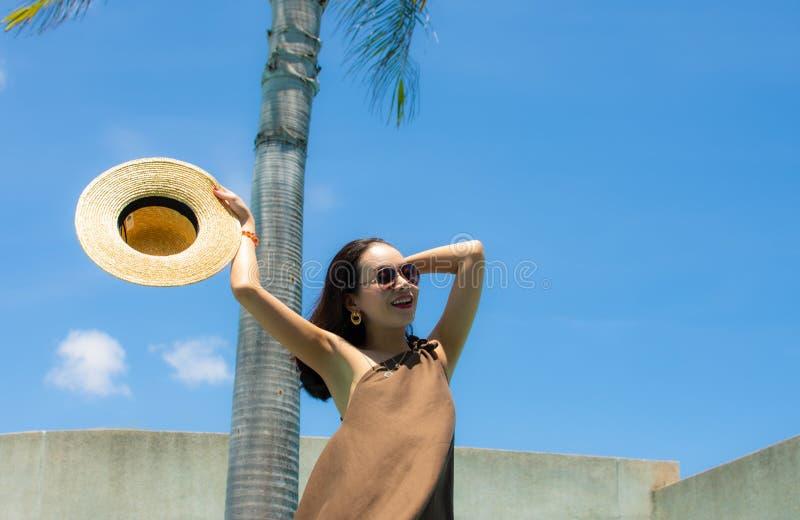 Una mujer hermosa está sosteniendo sombrero con el fondo del cielo foto de archivo