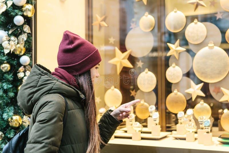 Una mujer hermosa joven elige un regalo de la Navidad foto de archivo libre de regalías