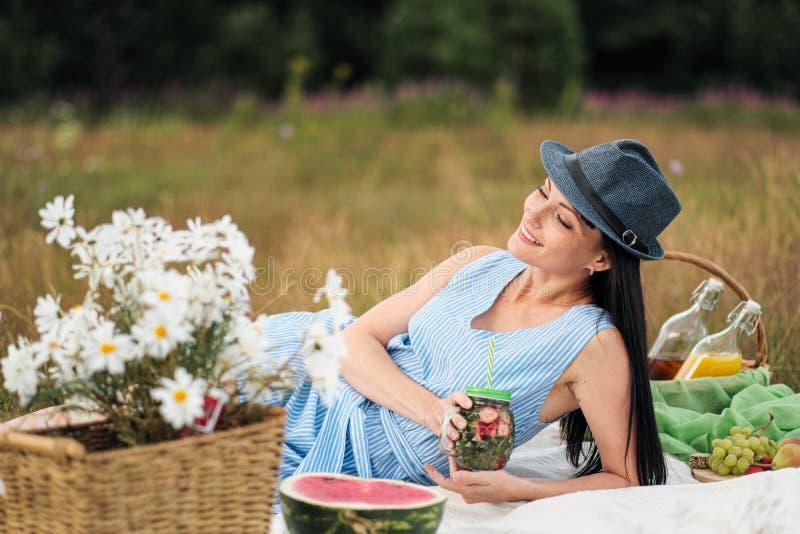 Una mujer hermosa joven en sombrero y vestido está bebiendo la limonada de un tarro de cristal, sentándose en la tela escocesa en imágenes de archivo libres de regalías