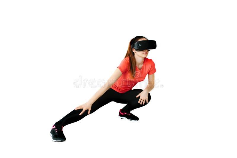Una mujer hermosa joven en vidrios de la realidad virtual hace aeróbicos remotamente Concepto futuro de la tecnología Proyección  foto de archivo