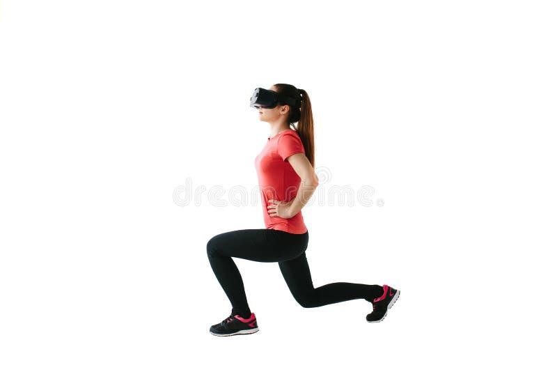 Una mujer hermosa joven en vidrios de la realidad virtual hace aeróbicos remotamente Concepto futuro de la tecnología Proyección  fotografía de archivo