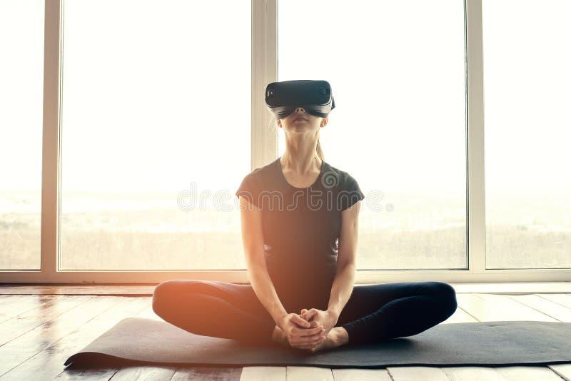 Una mujer hermosa joven en vidrios de la realidad virtual hace aeróbicos remotamente Concepto futuro de la tecnología Proyección  imágenes de archivo libres de regalías