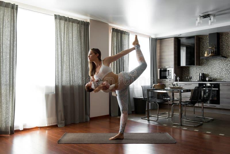 Una mujer hermosa joven que hace yoga con su hijo del bebé en la cocina imagenes de archivo