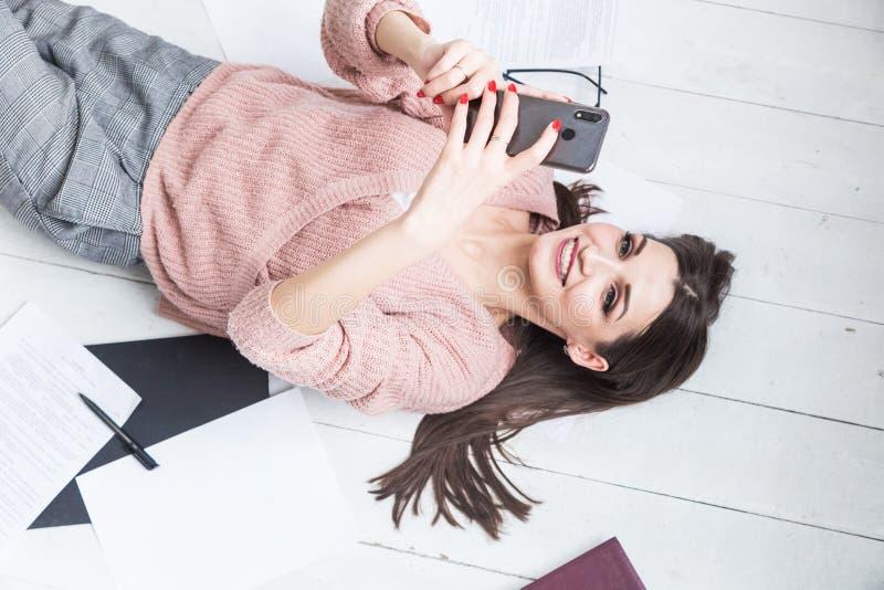 Una mujer hermosa miente en el piso entre los papeles y los documentos, el freelancer de la muchacha sonr?e y se relaja durante u imágenes de archivo libres de regalías