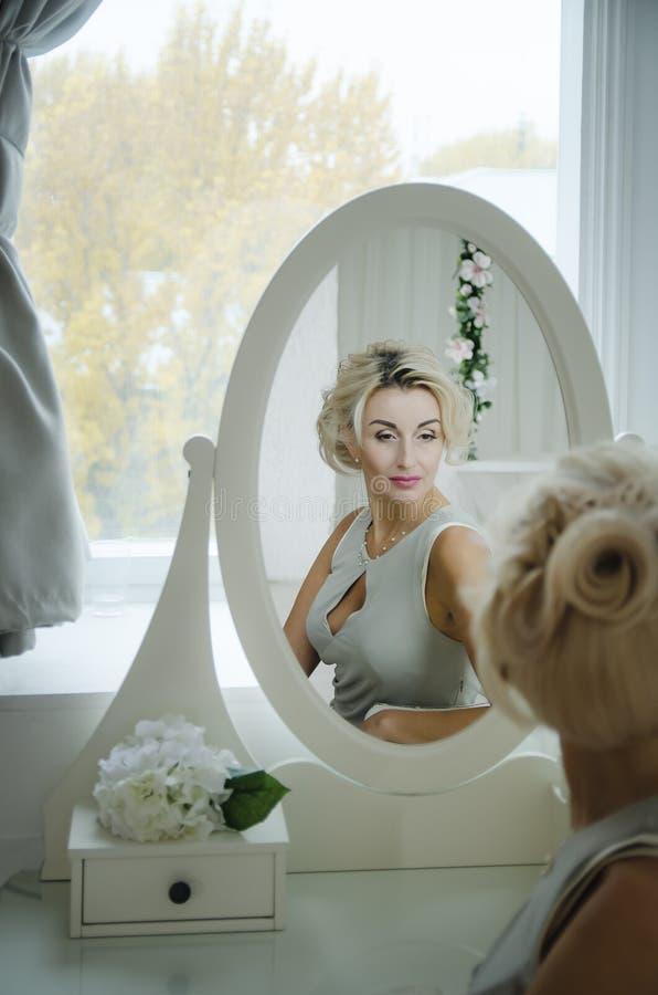 Una mujer hermosa mira en el espejo imagen de archivo