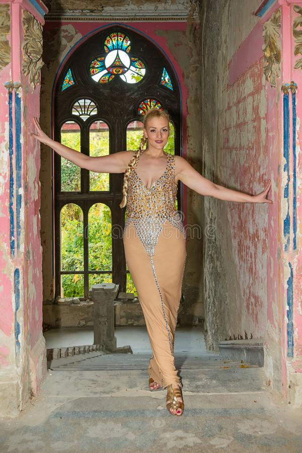 Una mujer hermosa presenta en un vestido festivo en el balcón de una muchacha abandonada del castleA en un vestido festivo en un  foto de archivo libre de regalías