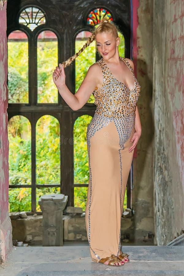 Una mujer hermosa presenta en un vestido festivo en el balcón de una muchacha abandonada del castleA en un vestido festivo en un  fotografía de archivo libre de regalías