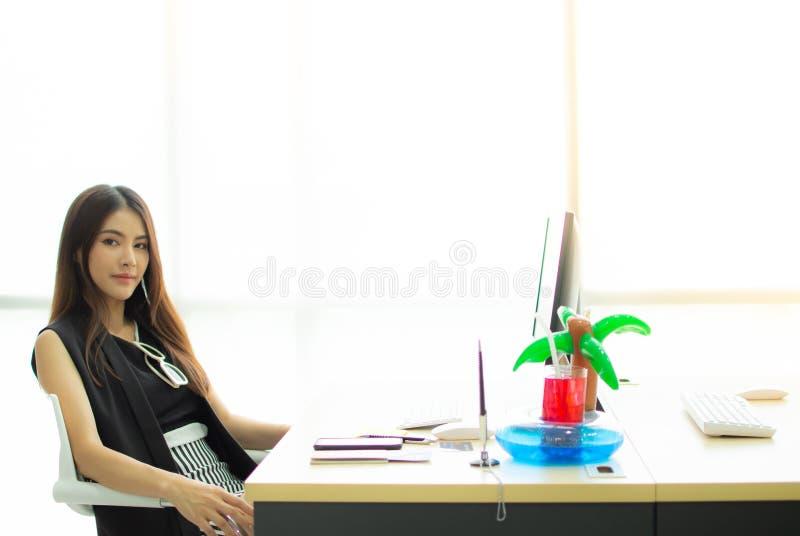 Una mujer hermosa que se sienta en la oficina y que planea para el viaje fotografía de archivo