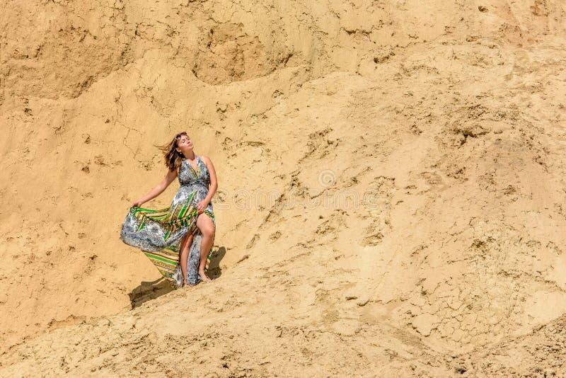 Una mujer hermosa se opone en un vestido y gafas de sol a una montaña arenosa fotos de archivo