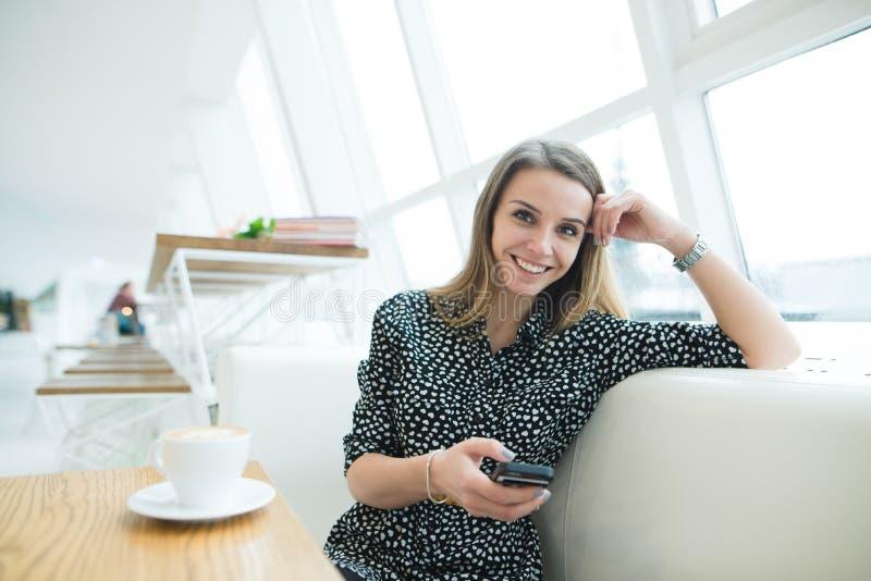 Una mujer hermosa sonriente se sienta en un café moderno elegante y utiliza un maratón Descanso para tomar café imágenes de archivo libres de regalías