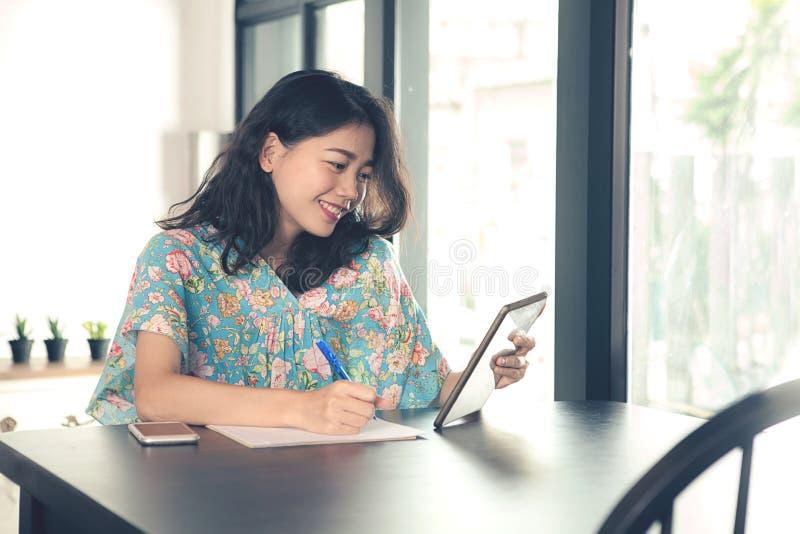 Una mujer independiente asiática más joven que mira a la pantalla de la tableta del ordenador imagen de archivo