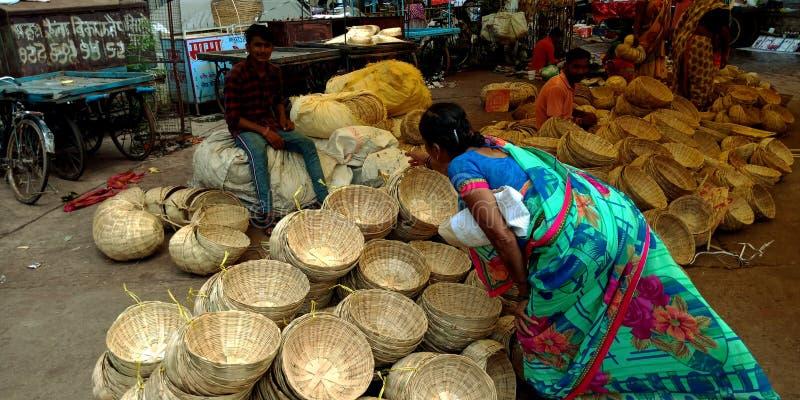 Una mujer india del pueblo que coge la cesta de madera en la tienda de la calle fotos de archivo libres de regalías