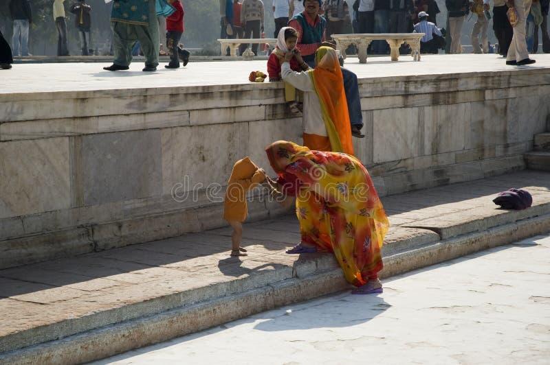 Una mujer india viste a su pequeño niño cerca del templo Familia india La India, Agra 31 de enero de 2009 foto de archivo libre de regalías