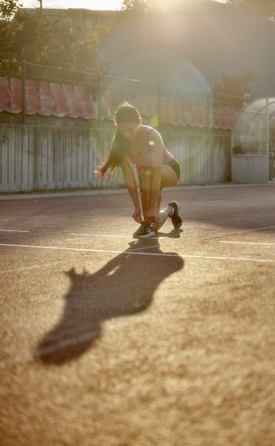 Una mujer joven, 20-29 años, atando sus cordones en pistas corrientes, ropa del deporte que lleva imagen de archivo libre de regalías