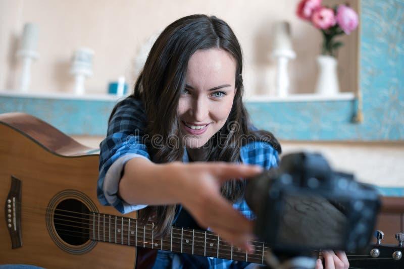 Una mujer joven ajusta el foco en la cámara para registrar un blog de la música con la guitarra foto de archivo