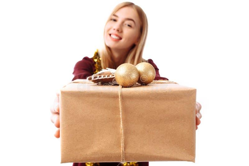 Una mujer joven alegre en un sombrero de Santa Claus que da una Navidad p fotografía de archivo libre de regalías