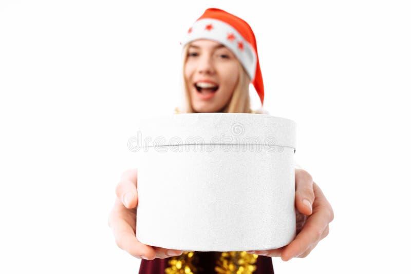 Una mujer joven alegre en un sombrero de Santa Claus que da una Navidad p fotografía de archivo