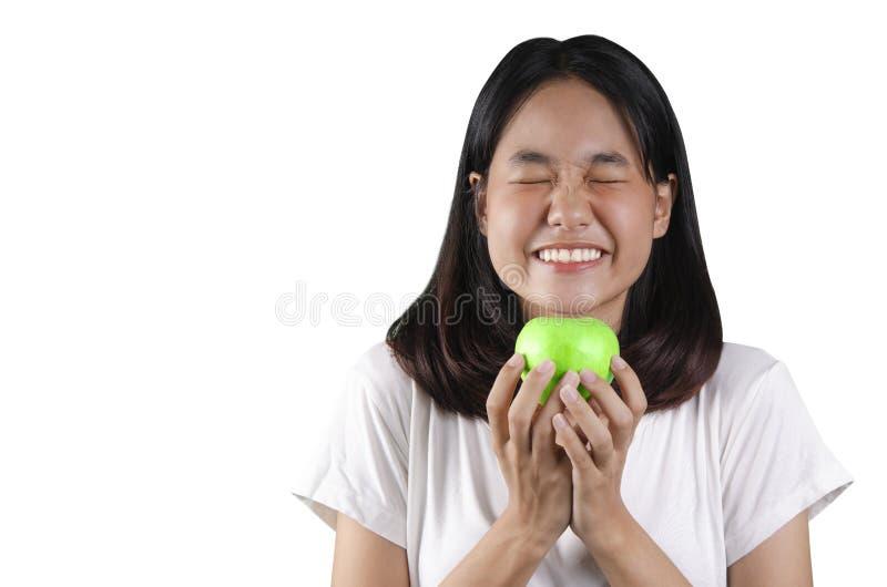 20 una mujer joven asiática que sostiene una manzana verde con el fondo blanco imagenes de archivo