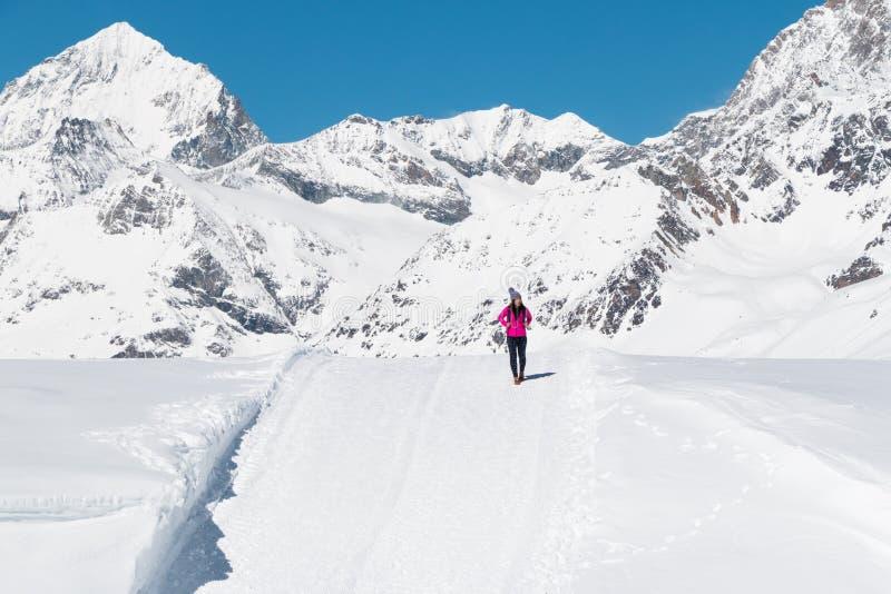 Una mujer joven asiática que viaja en la montaña de la nieve foto de archivo