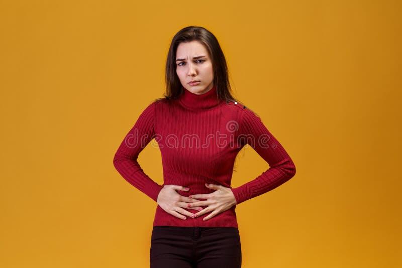 Una mujer joven atractiva asió su estómago del dolor de un abdomen más bajo, ciclo menstrual no da resto a hacer el trabajo fotos de archivo