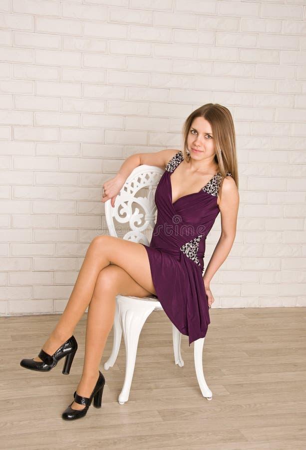 Una mujer joven atractiva que se sienta en la silla blanca imagen de archivo libre de regalías