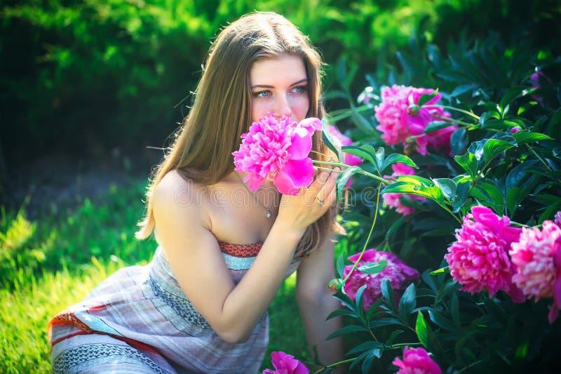 Una mujer joven atractiva sienta y goza del olor de flores fotografía de archivo