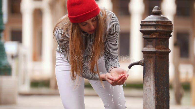 Una mujer joven bebe el agua de una fuente de la calle - relleno de sus manos de agua imagen de archivo