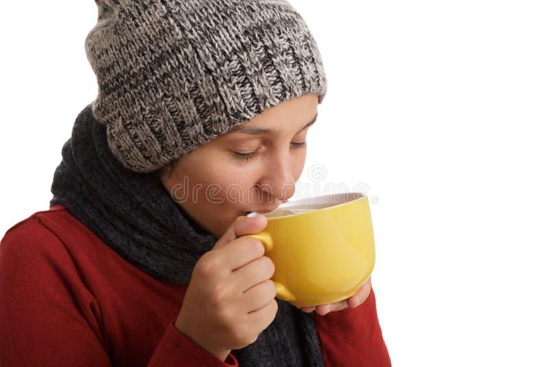 Una mujer joven bebe una taza de té caliente en invierno aislado en el fondo blanco imagen de archivo