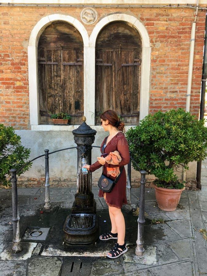 Una mujer joven bonita que llena encima de su botella de agua en un día de verano caliente en Burano, Italia en una fuente de agu fotos de archivo libres de regalías