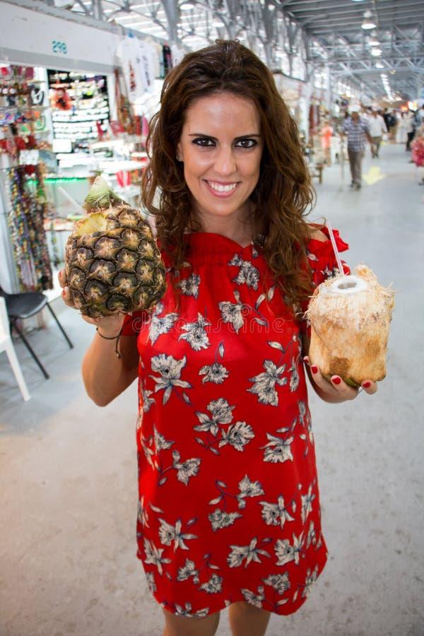 Una mujer joven bonita que lleva un vestido florecido rojo, llevando a cabo en sus manos bebidas naturales de una piña y del coco imagen de archivo
