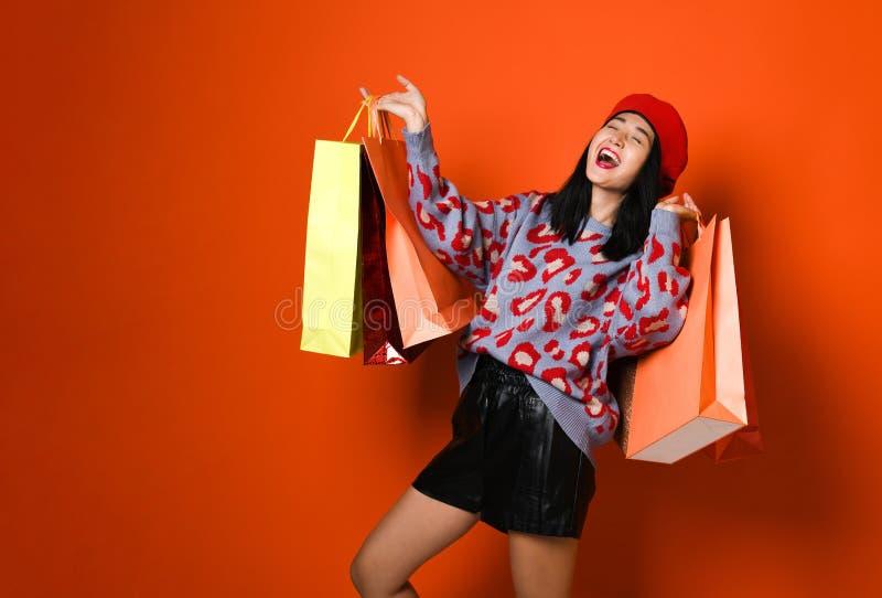 Una mujer joven bonita vestida elegante en un sombrero con los bolsos después de hacer compras imagen de archivo