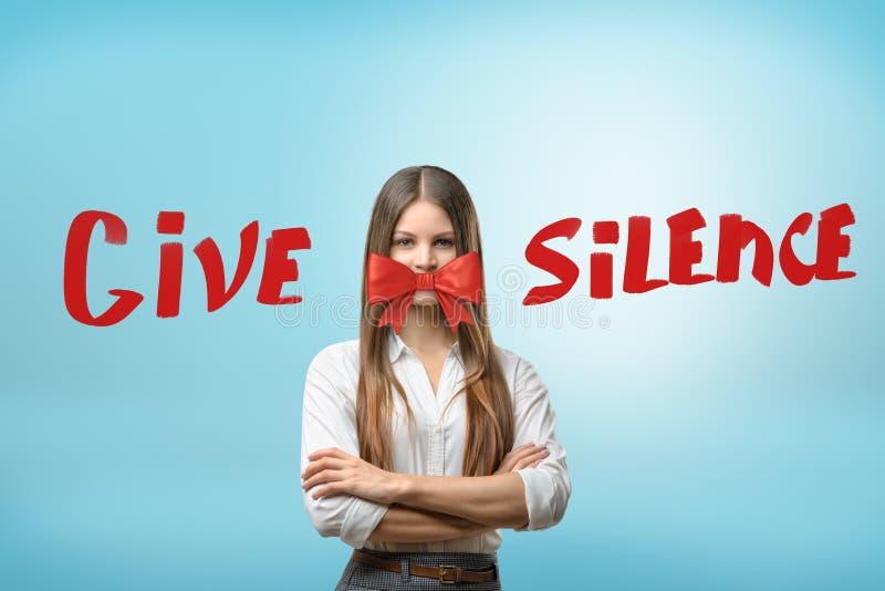 Una mujer joven, brazos dobló, con un arco rojo hermoso cubriendo su boca y el título 'da silencio ' fotos de archivo libres de regalías
