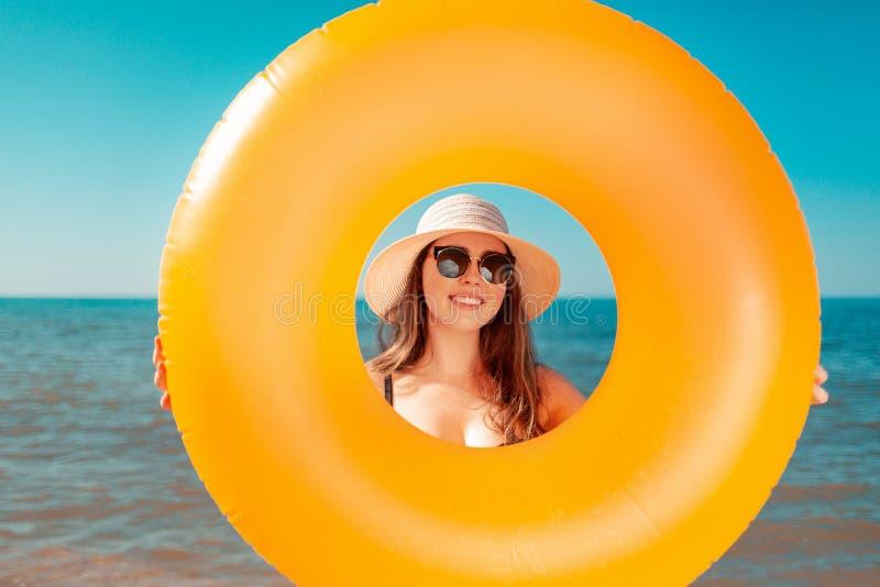 Una mujer joven bronceada celebra un círculo inflable anaranjado y miradas a través de él En el fondo es un mar El concepto de un imagen de archivo