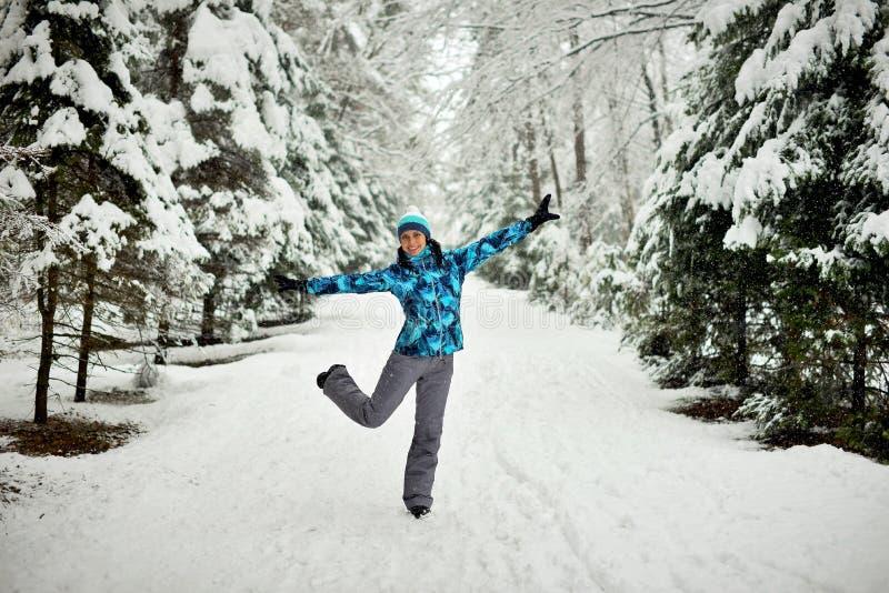 Una mujer joven camina en un bosque en un invierno nevoso imagen de archivo libre de regalías