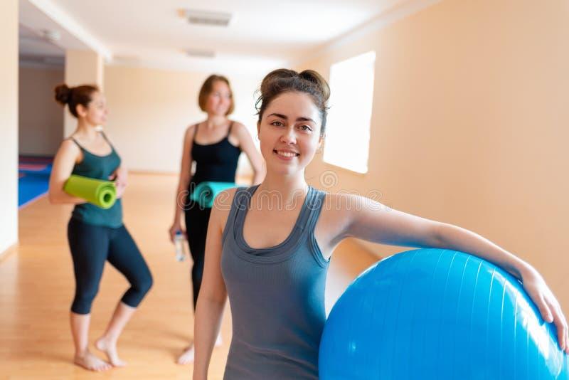 Una mujer joven con una bola gimnástica en sus manos que sonríe y que presenta para la cámara En el fondo hay dos mujeres con imagen de archivo libre de regalías