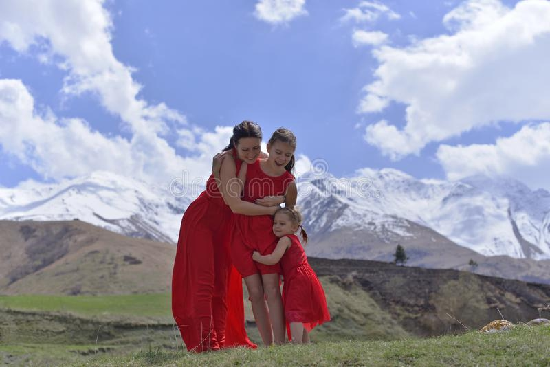 Una mujer joven con dos hijas en los vestidos rojos que descansan en las monta?as coronadas de nieve en la primavera fotos de archivo libres de regalías