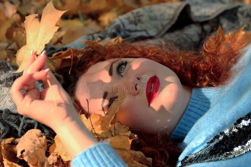 Una mujer joven con el pelo rojo está mintiendo en una manta y está mirando una hoja amarilla de un arce De la hoja baja un s her imágenes de archivo libres de regalías
