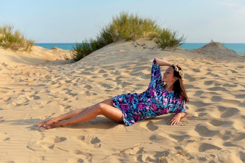Una mujer joven con una guirnalda de flores en su cabeza que descansa sobre una playa arenosa imagen de archivo