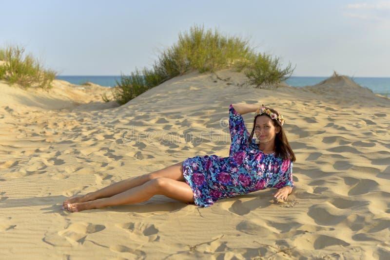 Una mujer joven con una guirnalda de flores en su cabeza que descansa sobre una playa arenosa fotos de archivo libres de regalías