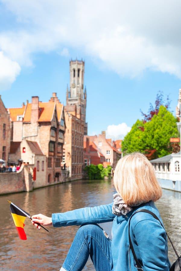 Una mujer joven con la bandera de Bélgica en sus manos está disfrutando de la vista de los canales en el centro histórico de fotografía de archivo libre de regalías