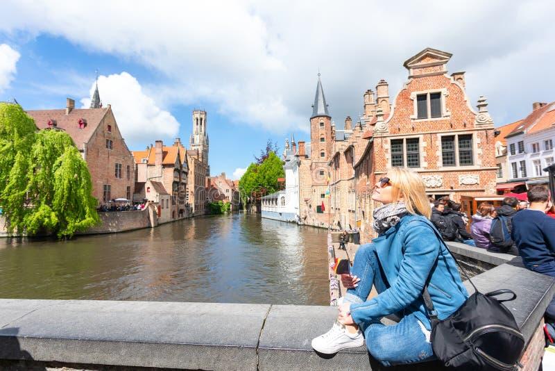 Una mujer joven con la bandera de Bélgica en sus manos está disfrutando de la vista de los canales en el centro histórico de fotografía de archivo