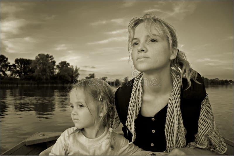 Una mujer joven con la niña está en un barco en un río fotos de archivo