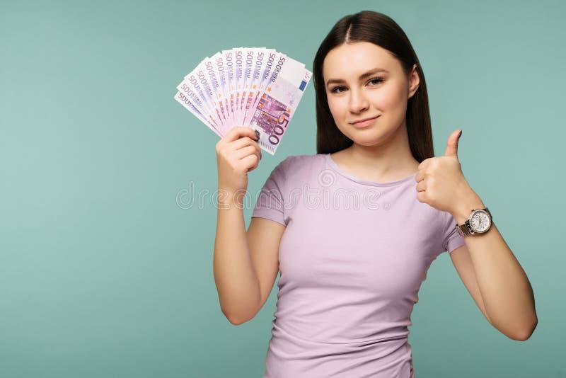 Una mujer joven con los dólares en sus manos y la autorización de g del showin, aisladas en fondo azul fotos de archivo libres de regalías